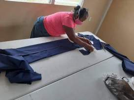 Another seamstress cuts the facemasks from fabric