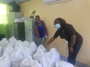 CDC volunteer Tashanna Legall presenting hampers to Shellon Swaving a teacher at the Wismar Resource Centre for the Blind