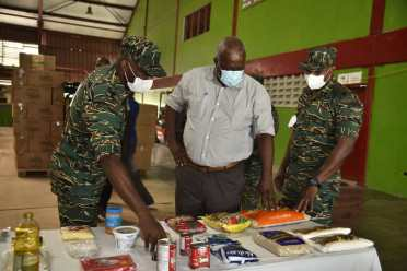 Prime Minister, Hon. (ret'd) Brigadier Mark Phillips is show some of the items that comprise the COVID-relief hampers during his visit to the CDC's storage facility