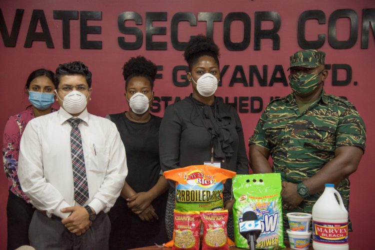 Staff of the Private Sector Commission [from left to right] Ravati Ramrattan, Executive Assistant, Economic Analyst, Joel Bhagwandin, Administrative Assitant, Christine are present as Tianna Graham, Public Relations Officer of the PSC, hands over a sample of the items to Logistics Officer of the CDC, Captain Michael Andrews.