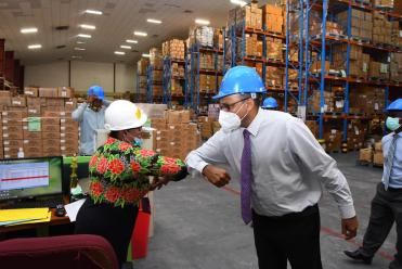 Minister of Health, Hon. Dr. Frank Anthony, greets the staff of the Supplies Chain Management Unit in Diamond, EBD in keeping with the COVID safety regulations