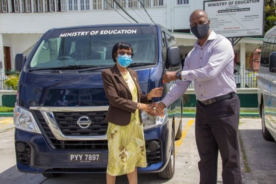 Executive Director of the Adult Education Association of Guyana, Mrs. Patricia David receiving the keys to the vehicle from Permanent Secretary, Mr. Alfred King