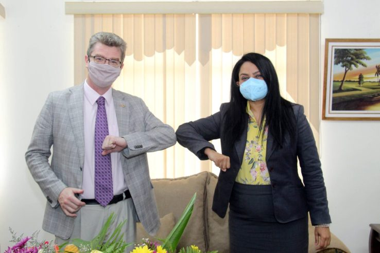 British High Commissioner to Guyana, His Excellency Greg Quinn, and Minister of Human Services and Social Security, Hon. Dr. Vindhya Persaud, greet each other in keeping with the COVID-19 safety protocols