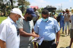 Minister of Housing and Water, Hon. Collin Croal (third from left) looks at official land documentation