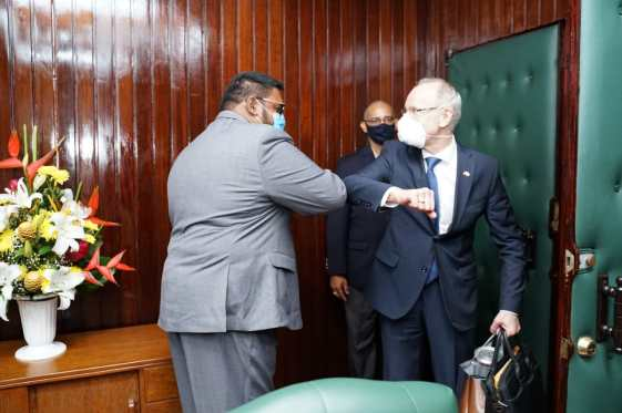 President Ali greets Mr. Alexander Kurmaz, Russian Ambassador to Guyana, during a courtesy earlier on Monday. The Guyanese Head of State and the Russian diplomat greeted each other in keeping with COVID 19 guidelines.