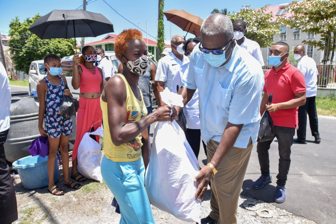Prime Minister Brigadier Mark Phillips presents a hamper to this Kingston resident, during the distribution exercise