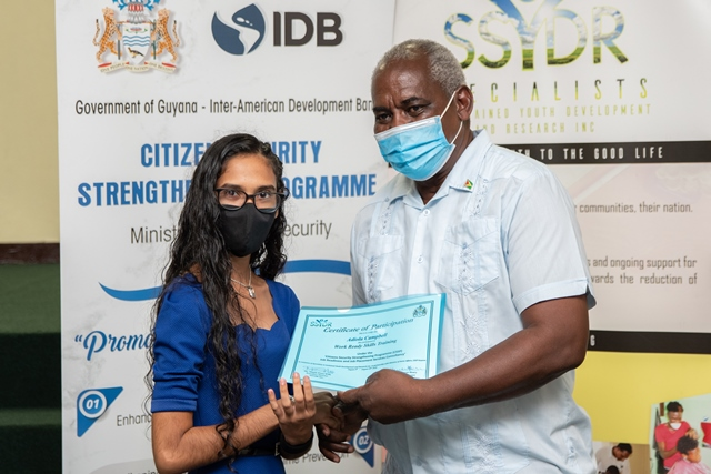 Minister of Home Affairs, Hon. Robeson Benn handing over a certificate to one of the graduates