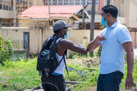 Minister of Culture, Youth and Sport, Hon. Charles Ramson Jr. greets a resident in the area