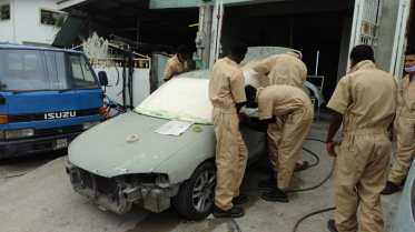 Some of the apprentices conducting body work repair on a vehicle