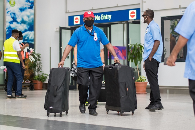 A member of the Red Cap Baggage Service at the CJIA conducting his duties.