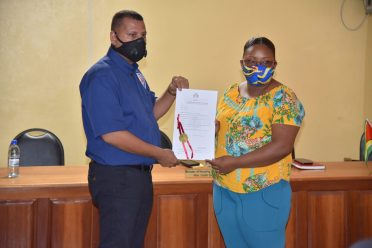 Minister of Housing and Water, Hon. Collin Croal, hands over a Certificate of Title to Land to Ms. Esther Haniff