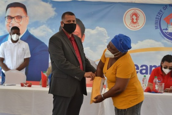 Mrs. Sheree Ross digs deep into for a house lot number in an envelope held by Minister of Housing and Water, Hon. Collin Croal, during the opening ceremony