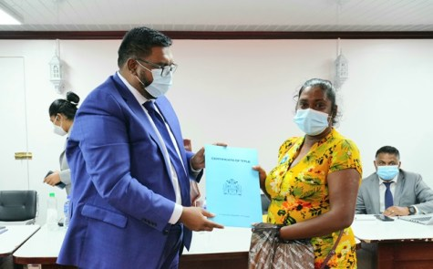 Ms. Pratima Sookdeo receiving her land title from President Dr. Mohamed Irfaan Ali during an outreach in Region Two.