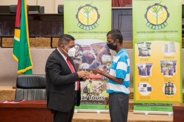 Minister of Agriculture, Hon. Zulfikar Mustapha presenting an employee with a token in honour of his years of service to GuySuCo