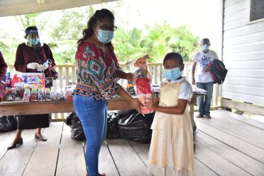 Regional Vice-Chairman of Region One, Ms. Annansha Peters presents a gift to one of the children Z:\2020\12 December\14 December 2020\Camera\Photos\Min Croal visit to Reg 1