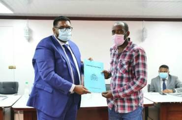 President Ali presents Mr Esaan Garraway with his Certificate of Title