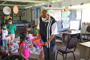 Minister of Public Works, Hon. Bishop Juan Edghill shares toys in riverine communities along the Berbice River