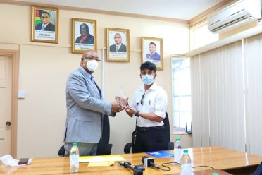 Minister of Public Works, Hon. Bishop Juan Edghill presents 19-year-old Captain Azam Ally with his licence today at a ceremony held in the Ministry's Boardroom.