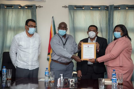 A representative of the Guyana National Bureau of Standard presents the certificate to PTCCB's Registrar, Ms. Trecia David and Minister of Agriculture, Hon. Zulfikar Mustapha. The Ministry's Director General Mr. Madanlall Ramraj is also pictured at right