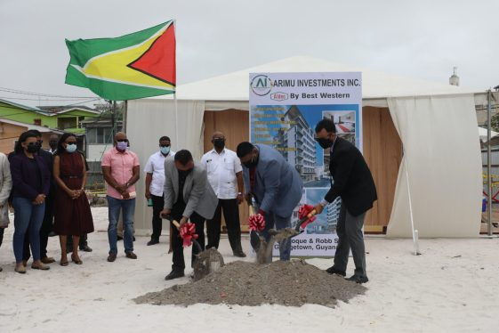 President Dr. Mohamed Irfaan Ali turning the sod for the Aiden Hotel with Chief Investment Officer and Chief Executive Officer of Guyana Office for Investment (G0-Invest) Dr. Peter Ramsaroop and Mr. Lorenzo Alphonso