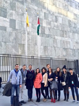 A group of Palestinian Journalists take a photo in front of the newly-raised Palestinian flag