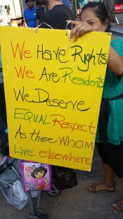 woman holding a sign that reads: we have rights, we are residents, we deserve equal respect as those who live elsewhere