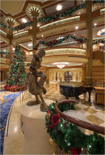 "Holidays are magical aboard the Disney Dream, where the magnificent atrium lobby is transformed into a winter wonderland. In the spirit of holiday cheer, Disney Cruise Line adds sparkle to each ship during Very Merrytime Cruises, with special stem-to-stern holiday events, traditional ""turkey day"" fanfare, Christmas feasts, ""snow flurries"" and New Year's Eve galas. (Kent Phillips, photographer)"