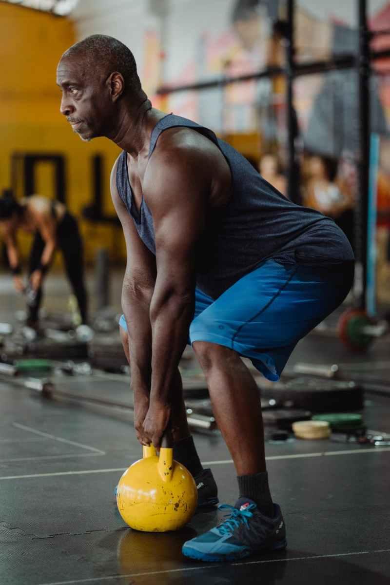 photo of man using yellow kettlebell