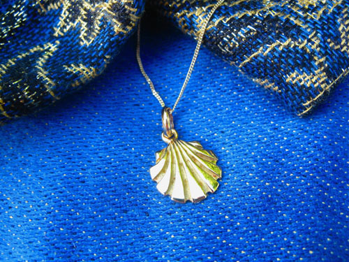 Picture showing the scallop shell hanging on an 18ct gold curb chain