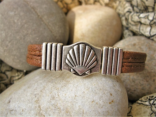The bracelet fastens with a unique scallop shell clasp