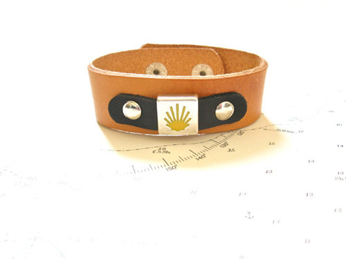 This eye-catching cuff bracelet features the stylised yellow scallop shell of Santiago de Compostela