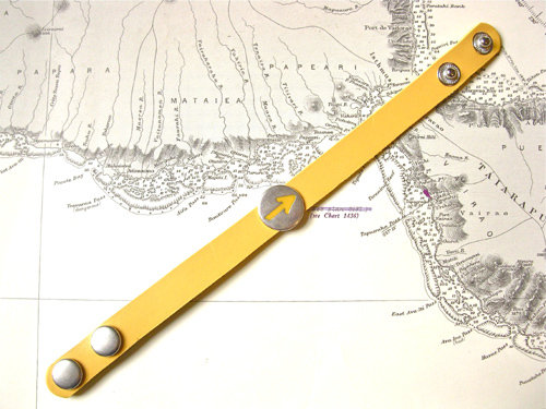 The yellow leather bracelet fastens with poppers and measures approx 14mm wide