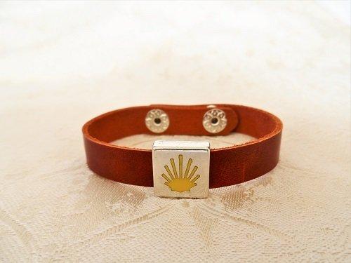 Rich brown leather bracelet showing the Way of St James waymarker symbol