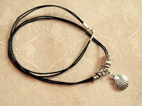 The metal scallop shell charm and beads hang on a thin, black double corded necklace
