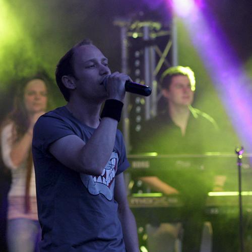 Ein Sänger mit Mikrofon und dahinter ein Mann am Keyboard