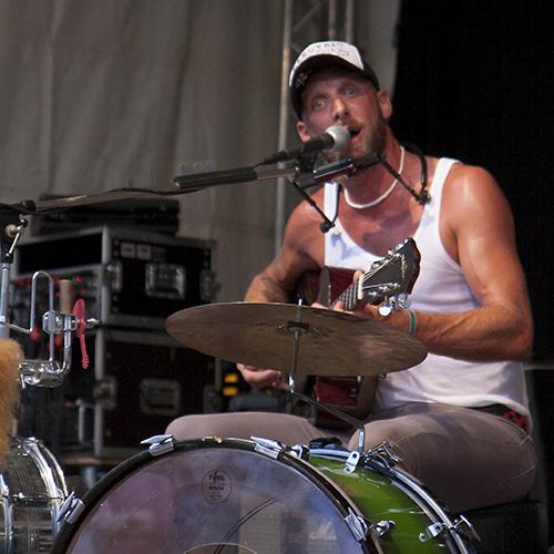 Ein Mann sitzt am Schlagzeug und singt