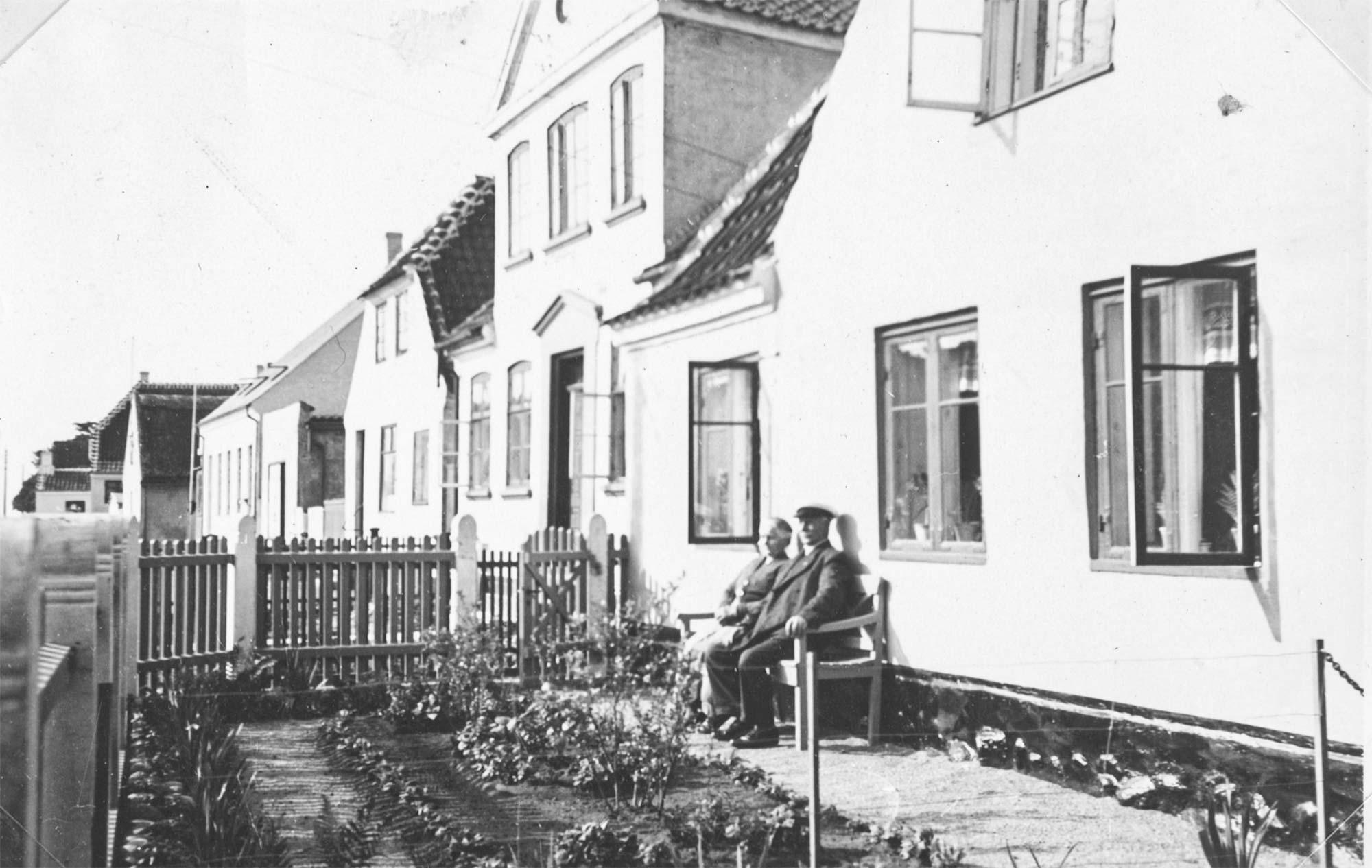 Emma og Jens Andersen i Kampensgade 4. De ses i forhaven ud til Strandlinien. 1935. Foto: Historisk Arkiv Dragør.