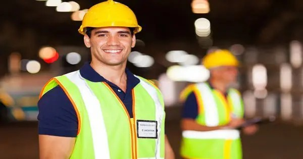 Construction Worker Smiling with background of other workers
