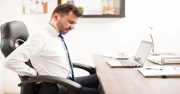 Man in office chair with low back pain