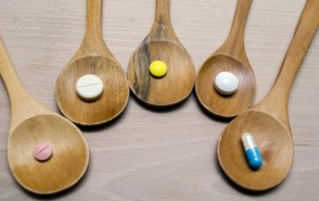 Different pills and tablets on wooden spoons