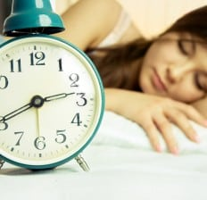 woman sleeping peacefully in bed, alarm clock