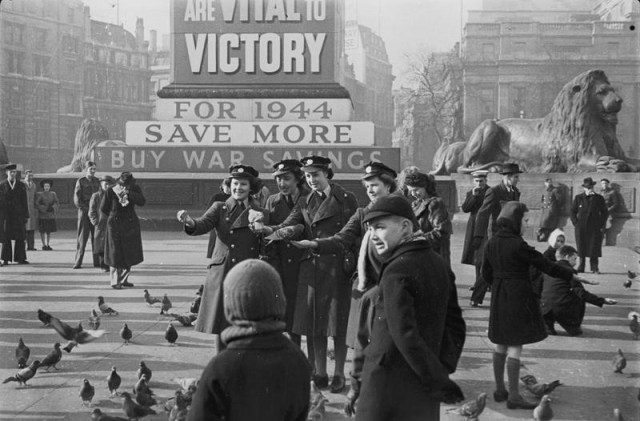 Members of the Women's Auxiliary Air Force and children are amongst those feeding the pigeons in Trafalgar Square in London. In the background, the base of Nelson's Column is covered in War Savings posters and one of the Trafalgar Square lions can also be seen. D 18302 Part of MINISTRY OF INFORMATION SECOND WORLD WAR OFFICIAL COLLECTION Ministry of Information Photo Division Photographer