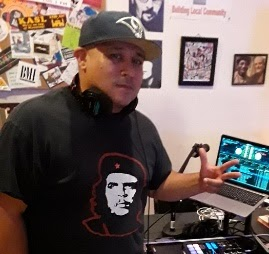 Man in shorts, t shirt and a ball cap with headphones around his neck stands over a turntable