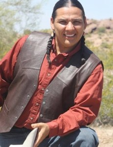 A handsome, smiling man in a leather vest with his hair in two braids and a cowboy hat in his hand.