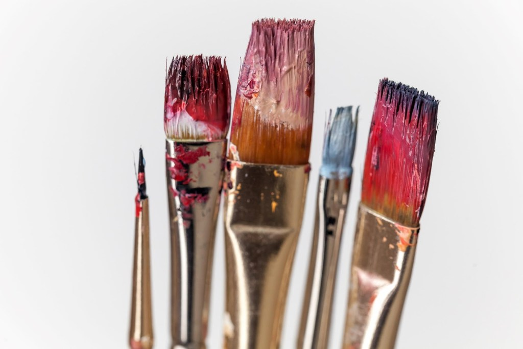 the tops of five paint brushes loaded with paint against a white backdrop
