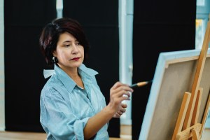 a handsome woman with dark hair standing in front of an easel and painting on a canvas