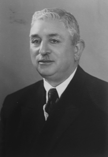 Black and White photo of a distinguished older man with white hair and a small moustache. He wears a dark suit, white shirt and tie.
