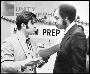 Two men facing in conversation, one white, one black, with the banner of the Harlem Prperp School in the background