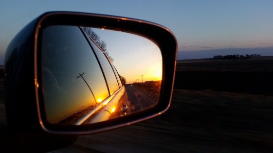 image of a side mirror on a car showing the reflection of the side of the car