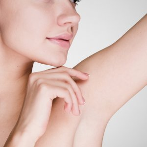 young girl on a white background caring for the skin underarms